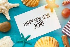 Fundo com shell, estrela do mar do ano novo feliz em um azul de madeira imagens de stock royalty free