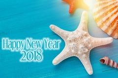 Fundo com shell, estrela do mar do ano novo feliz em um fundo azul de madeira fotos de stock royalty free