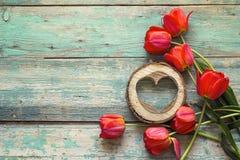 Fundo com tulipas vermelhas e corações de madeira na placa de madeira velha Fotografia de Stock Royalty Free