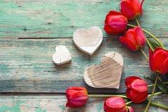 Fundo com tulipas vermelhas e corações de madeira na placa de madeira velha Imagens de Stock Royalty Free