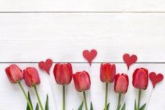 Fundo com tulipas vermelhas e corações decorativos em de madeira branco Imagens de Stock Royalty Free