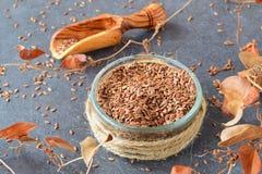 Fundo com um espaço para o texto Uma bacia de vidro de sementes de linho com a colher verde-oliva cercada por flores artificiais  Imagens de Stock