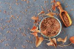 Fundo com um espaço para o texto Uma bacia de vidro de sementes de linho com a colher verde-oliva cercada por flores artificiais  Fotografia de Stock