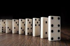 Fundo criativo, dominó branco, no fundo de madeira marrom Conceito do efeito de dominó, reação em cadeia ilustração do vetor