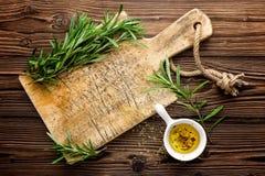 Fundo culinário com os ingredientes da placa de madeira e do cozimento, azeite e alecrins, acima da vista, espaço para um texto Imagens de Stock