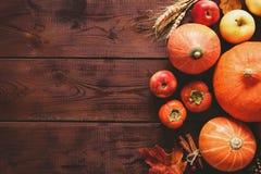 Fundo da ação de graças com abóboras, maçãs e as folhas caídas na tabela de madeira Imagem de Stock