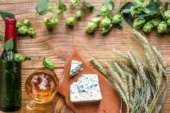 Fundo da cerveja Cerveja fresca e o queijo salgado em uma tabela de madeira Vista superior Imagens de Stock