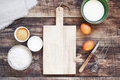 Fundo da cozinha com placa de corte de madeira velha vazia e os ingredientes orgânicos foto de stock