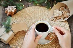 Fundo da decoração do feriado do Feliz Natal Um copo do café quente do café nas mãos de uma moça com caseiro tradicional imagem de stock