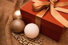 Fundo da decoração do Natal, caixa de presente com fita e brinquedos da árvore no pano de saco Tema do ano novo fotos de stock