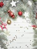 Fundo da decoração do Natal ou do ano novo: ramos da pele-árvore, bolas de vidro coloridas e estrelas de brilho no branco Fotos de Stock