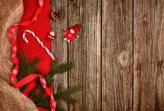 Fundo da decoração do Natal sobre a tabela de madeira com o pano vermelho e de linho Fotografia de Stock