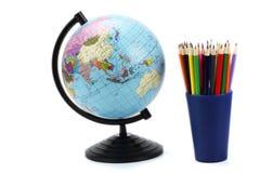 Fundo da escola Globo com os lápis coloridos isolados no fundo branco Foto de Stock