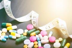 Fundo da farmácia em uma tabela preta com fita de medição Tabuletas em um fundo preto Comprimidos Medicina e saudável Feche acima fotografia de stock