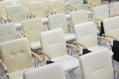 Fundo da fileira vazia das cadeiras brancas na sala de conferências imagens de stock royalty free
