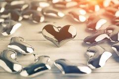 Fundo da forma do coração do metal no assoalho de madeira com a iluminação ef Imagem de Stock Royalty Free