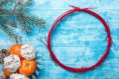 Fundo da madeira dos azuis celestes Árvore de abeto verde Fruto com o mandarino e os doces Círculo pelo Natal ou o ano novo Imagens de Stock Royalty Free