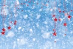Fundo da neve do Feliz Natal com estrelas e o floco de neve de suspensão Fotos de Stock