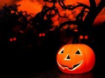 Fundo da noite de Dia das Bruxas com os olhos vermelhos assustadores e a abóbora Imagem de Stock Royalty Free