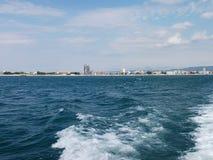 Fundo da onda do verão da superfície do Mar Negro Vista do iate Seascape exótico com nuvens e cidade no horizonte Tranquilidade d Foto de Stock Royalty Free