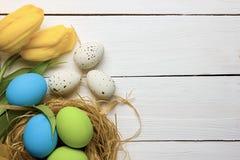 Fundo da Páscoa com os ovos coloridos no ninho e as tulipas amarelas sobre a madeira branca Vista superior com espaço da cópia fotografia de stock