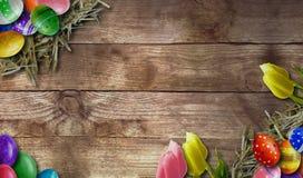 Fundo da Páscoa com os ovos da páscoa na placa de madeira Imagens de Stock