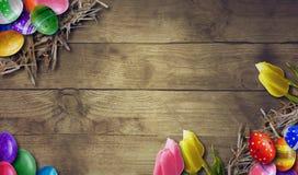 Fundo da Páscoa com os ovos da páscoa na placa de madeira Foto de Stock