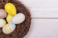 Fundo da Páscoa com os ovos no ninho sobre a madeira branca Vista superior com espaço da cópia imagens de stock royalty free