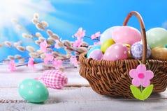 Fundo da Páscoa com os ovos pintados na cesta de vime contra o bl Imagens de Stock