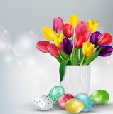 Fundo da Páscoa com ovos e as tulipas coloridos no vidro Fotografia de Stock Royalty Free