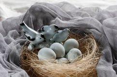 Fundo da Páscoa com pássaros e os ovos decorativos no ninho Foto de Stock