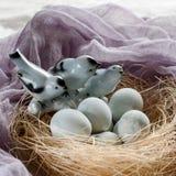 Fundo da Páscoa com pássaros e os ovos decorativos no ninho Fotos de Stock