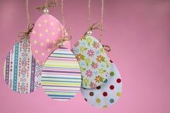 Fundo da Páscoa feito a mão Grupo de ovos coloridos feitos do cair de papel em uma corda em um fundo cor-de-rosa imagem de stock