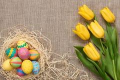 Fundo da Páscoa, ovos, tulipas amarelas no pano de saco Foto de Stock Royalty Free