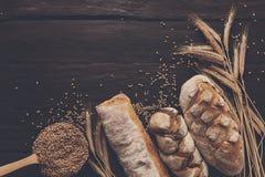Fundo da padaria do pão Brown e composição branca dos nacos da grão do trigo Imagem de Stock Royalty Free