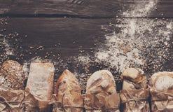 Fundo da padaria do pão Brown e composição branca dos nacos da grão do trigo Fotos de Stock Royalty Free