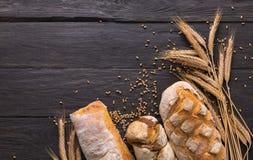 Fundo da padaria do pão Brown e composição branca dos nacos da grão do trigo Imagem de Stock
