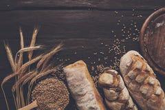 Fundo da padaria do pão Brown e composição branca dos nacos da grão do trigo Fotografia de Stock Royalty Free