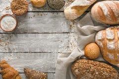 Fundo da padaria do pão Brown e composição branca dos nacos da grão do trigo na madeira rústica Imagem de Stock Royalty Free