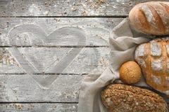 Fundo da padaria do pão Brown e composição branca dos nacos da grão do trigo na madeira rústica Fotografia de Stock
