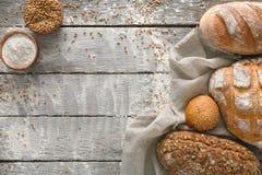 Fundo da padaria do pão Brown e composição branca dos nacos da grão do trigo na madeira rústica Fotos de Stock