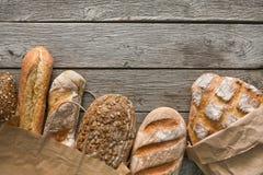 Fundo da padaria do pão Brown e composição branca dos nacos da grão do trigo na madeira rústica Imagens de Stock Royalty Free
