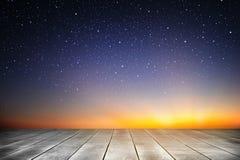 Fundo da prancha de madeira e da noite estrelado no tempo do nascer do sol Imagens de Stock