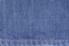 Fundo da textura da tela das calças de brim da sarja de Nimes com a emenda para o projeto Fotos de Stock Royalty Free