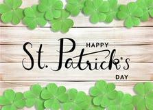 Fundo da tipografia do texto do preto do dia de St Patrick feliz com os trevos verdes na textura de madeira fotos de stock royalty free