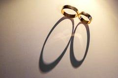 Fundo das alianças de casamento A luz passa através das alianças de casamento e forma uma sombra Fotografia de Stock