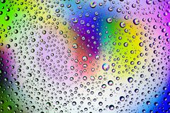 Fundo das gotas no vidro e nos cursos multi-coloridos da pintura fotos de stock
