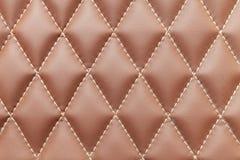 Fundo de couro e textura de Brown costurados com as linhas romboidais brancas como um teste padrão para o interior do veículo fotos de stock royalty free