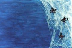 Fundo de Dia das Bruxas com Web de aranha e aranhas como símbolos de Dia das Bruxas na obscuridade - fundo de madeira azul Imagens de Stock