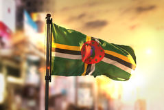 Fundo de Dominica Flag Against City Blurred no nascer do sol Backlig fotografia de stock